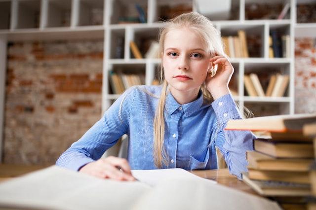 Mladé dievča s blond vlasmi sedí pri stole s kopou kníh.jpg