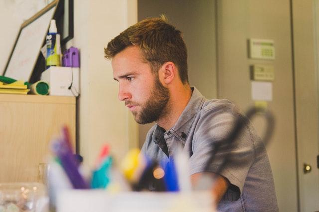 Študent sedí za pracovným stolom v izbe.jpg