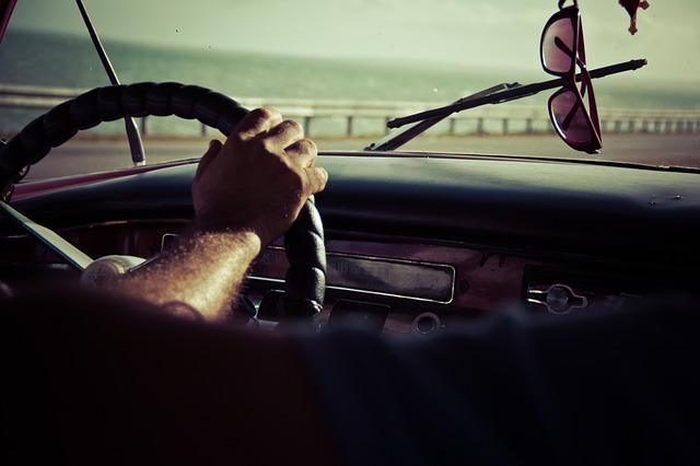 Človek drží volant auta a šoféruje.jpg