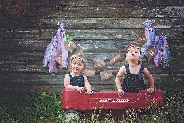 Dve malé deti sedia v červenom malom autíčku.jpg