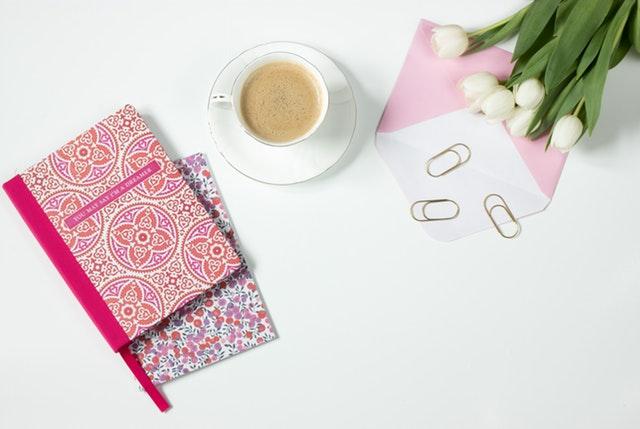 Šálka s kávou, ružové zápisníky, obálka, spinky a biele tulipány.jpg