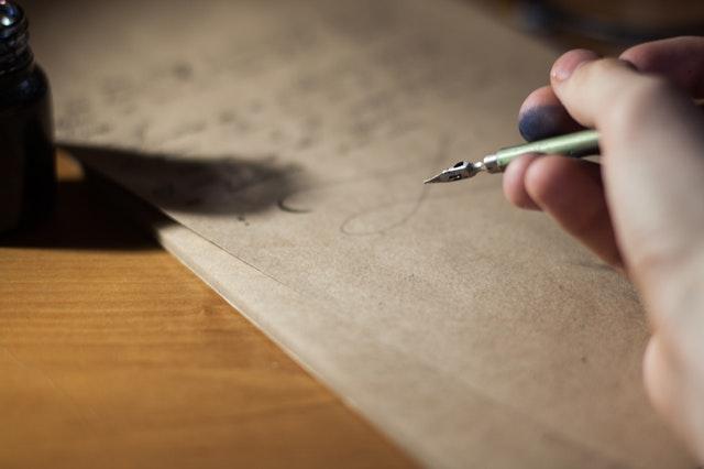Človek, ktorý píše atramentovým perom na hnedý papier.jpg