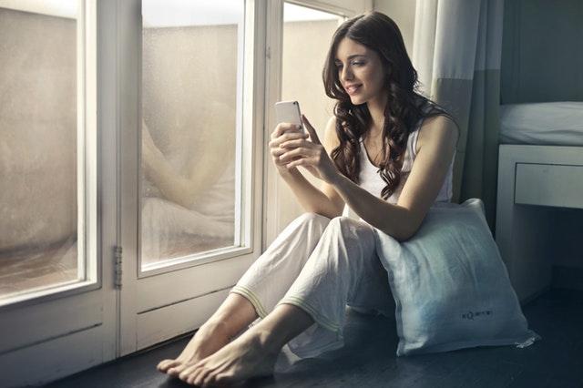 Žena sedí pri okne s vankúšmi a telefonuje